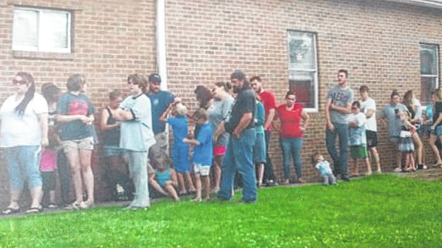 Families line to receive donated school supplies.