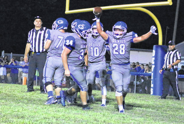 Gallia Academy senior Lane Pullins (28) celebrates with his teammates after scoring a third quarter touchdown against Meigs on Friday night in a Week 1 football contest at Memorial Field in Gallipolis, Ohio.