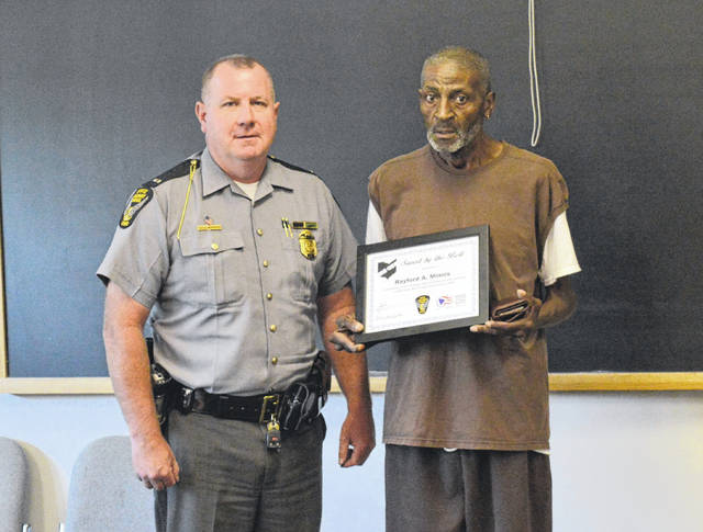 Ohio State Highway Patrol Gallipolis Post Commander Lt. Barry Call stands next to Saved by the Belt Award winner Rayford Minnis.