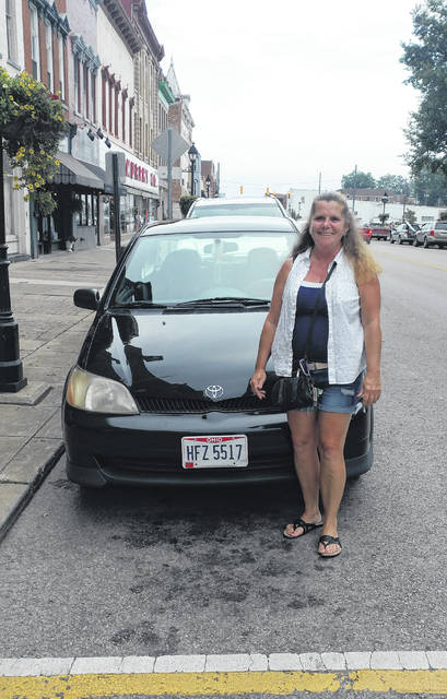 Pamela Hopkins stands with her repaired Toyota Echo.