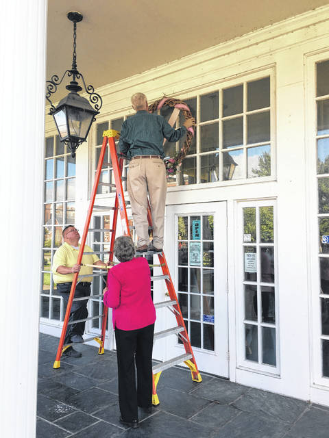 Commissioner Rick Handley had the honor of hanging the Breast Cancer Awareness wreath above the Mason County Library's entrance way.