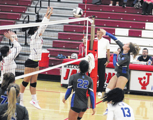 Gallia Academy senior Aubrey Unroe, right, hits a spike attempt during Game 3 of Monday night's volleyball match against Jackson in Jackson, Ohio.