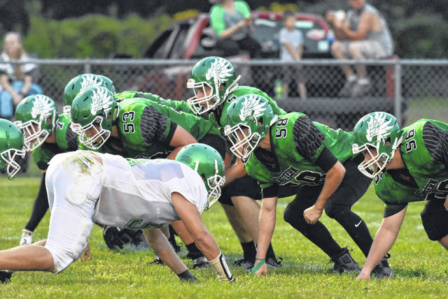 Eastern senior Isaiah Fish (5) prepares to take the snap from Jake Barber (53), during the Eagles' opening week loss to Huntington Ross on Aug. 24 in Tuppers Plains, Ohio.