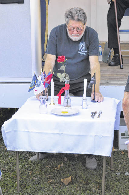 VFW 4464 member Keith Sheets stands watch over the ceremonial POW and MIA Empty Chair and Table during a windy Friday morning.