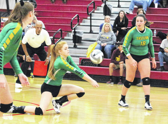Eastern senior Ally Barber, middle, digs up a serve during Game 3 of Saturday's Division IV district volleyball final against Portsmouth Clay at Jackson High School in Jackson, Ohio.