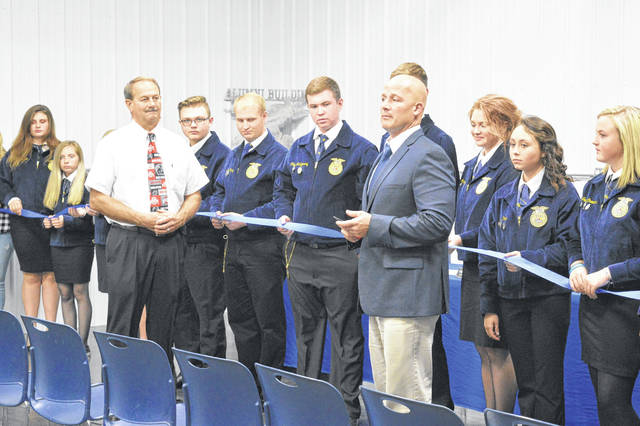 Gallipolis FFA members dedicated their new Gallipolis FFA Alumni Building behind Gallia Academy High School in Centenary Wednesday evening. Gallipolis City Schools Superintendent Craig Wright, right, addresses the assembled with FFA Alumni Treasurer Tim Massie, left, before the cutting of the ribbon. The building will be dedicated to the storage of FFA equipment and will be utilized as temporary housing for animals to teach students how to judge livestock. Massie said the building was built in part from funds raised by FFA alumni over the past two decades. Other donations were made by the Gallia agricultural community.