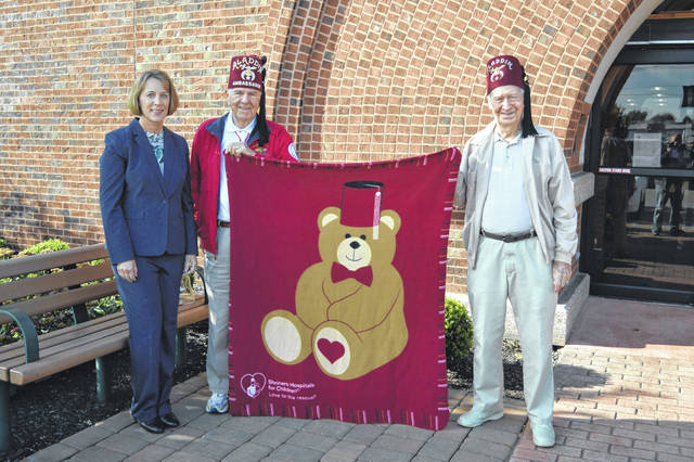 Gallipolis Shriners donated a blanket to Bossard Memorial Library as the facility serves as an information and contact point for the organization. From left to right stand Bossard Memorial Director Debbie Saunders, Guy Guinther and Homer Hankins. Both members are associated with the Aladdin Temple in Columbus and emphasized that part of a Shriner member's mission was to support families and that is accomplished through the support of Shriners Hospitals for Children. Guinther and Hankins said that if a family was in need, they could contact the hospital and the Gallipolis Shriners would assist in transporting a family to a local Shriner Hospital and it did not cost a family for a child to seek treatment. The library can be contacted at (740) 446-7323.