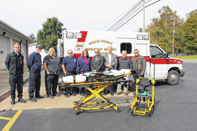 Gallia Commissioners Dave Smith, Harold Montgomery and Brent Saunders along with Gallia EMS Director Larry Boyer and colleague squad members display a new stair chair, right, and power loading stretcher, left.