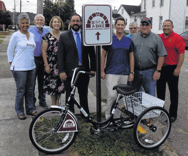 A new trike-style bicycle recently began circulating through Bossard Library's popular Book-a-Bike program. Pictured, from left, are: Gallia County District Library Board of Trustees Elaine Armstrong (Vice President), Jay Caldwell, Library Director Debbie Saunders, Graham Woodyard, Traci Good, Larry Shong (Secretary), Robbie Jenkins (President), and O. O. McIntyre Park District Director Paul Covey.