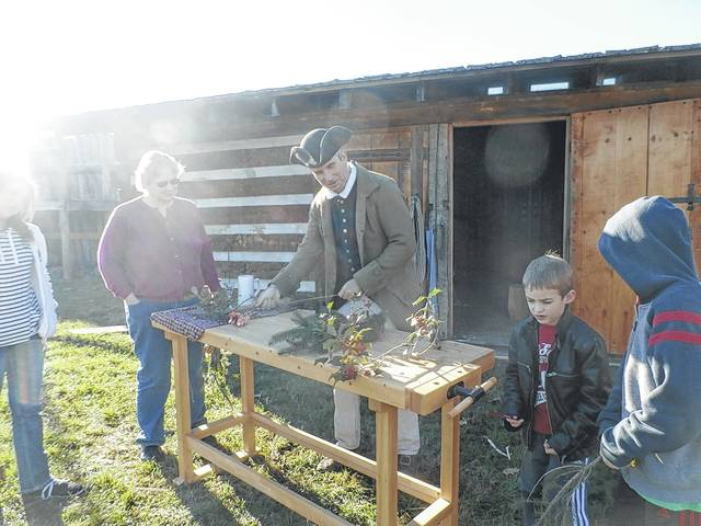 Craig Hesson, reenactor and volunteer at Fort Randolph, shows visitors how to make gifts suitable for those living in the 1700's at a past Christmas on the Frontier event. This year, festivities are set for this Saturday, Dec. 1.