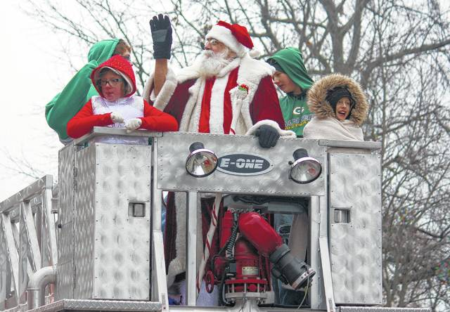 The City Park Santa Claus Chester Polcyn rides on the Gallipolis Fire Department Ladder truck during the 2015 Gallipolis Christmas Parade.