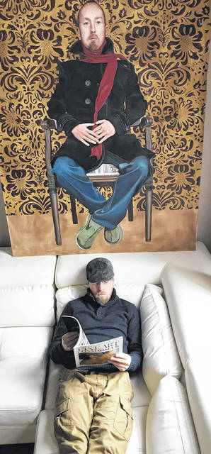 Jamie Sloane reads below the watchful eyes of Jamie Sloane in his fourth floor studio/penthouse in the Lowe Hotel in a photo taken earlier this spring. This self portrait done of himself includes Nike tennis shoes and swirling ideas.