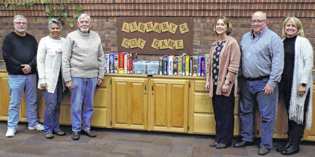 Patrons of Bossard Library can now choose from among a myriad of board and card games to check out all for free with their library cards. Pictured are members of the library's Board of Trustees and the library director with the library's collection of games. From left, are: Larry Shong, secretary; Elaine Armstrong, vice president; Jay Caldwell, member; Debbie Saunders, library director; Robbie Jenkins, president; and Leanna Martin, member.