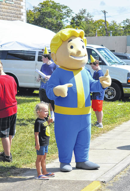 One young woman poses with Fallout's Vault Boy, mascot of the Vault-Tech corporation in the Fallout gaming universe during the Mothman Festival.