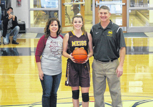 MHS senior Kassidy Betzing, with parents Kim Betzing (left) and Cary Betzing (right), is presented the game-ball after surpassing the career 1,000-point mark, during Saturday's River City Classic in Marietta, Ohio.