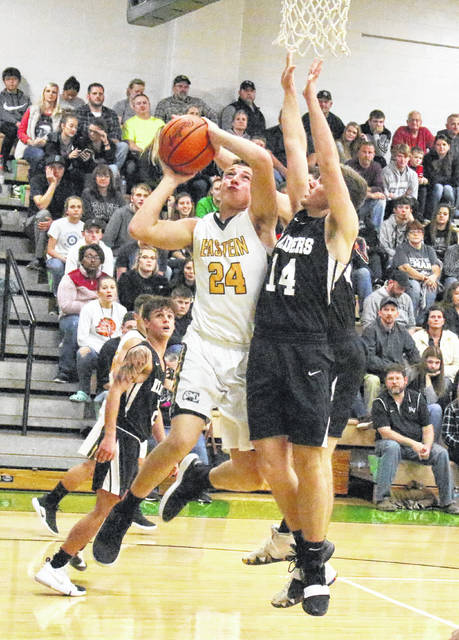 Eastern junior Mason Dishong (24) goes in for a contested shot attempt over River Valley defender Chase Caldwell (14) during the first half of Friday night's season opening boys basketball contest the Eagle's Nest in Tuppers Plains, Ohio.
