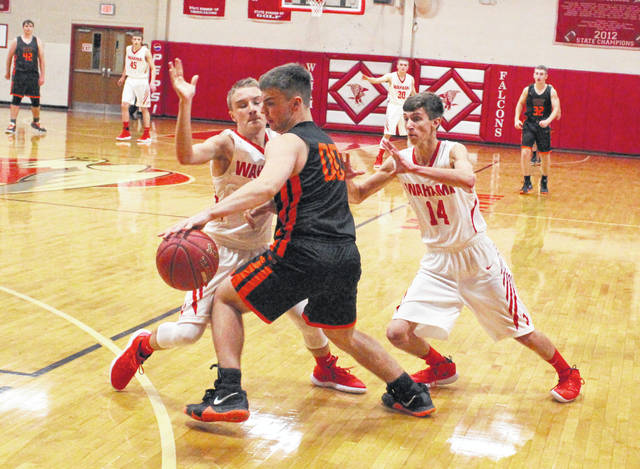 Wahama defenders Brayden Davenport, left, and Jonathan Frye (14) trap a Wirt County ball-handler during a Dec. 4 boys basketball contest at Gary Clark Court in Mason, W.Va.