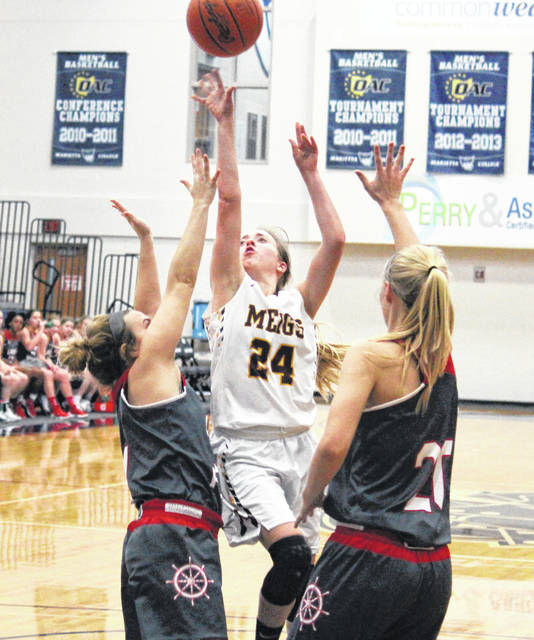 MHS senior Madison Fields (24) tries a two-pointer in between a pair of Lady Pilots, during the Lady Marauders' 10-point setback on Friday in Marietta, Ohio.