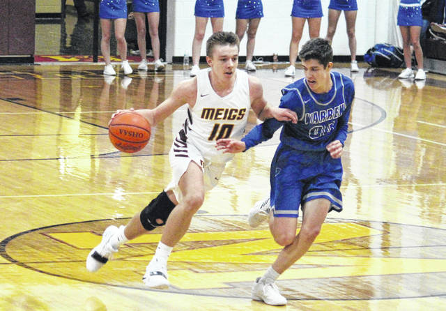Meigs freshman Coulter Cleland (10) drives past Warren's Kurt Taylor (00), during the Warriors' 63-48 victory on Tuesday in Rocksprings, Ohio.