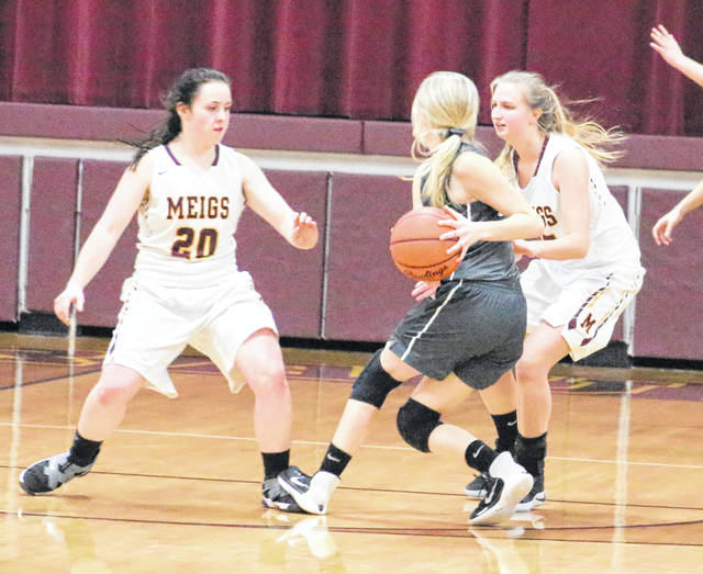 Meigs defenders Alyssa Smith (20) and Olivia Haggy trap River Valley's Sierra Somerville during the second half of Monday night's girls basketball contest at Larry R. Morrison Gymnasium in Rocksprings, Ohio.