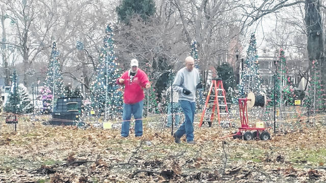 Area residents inspect lights in Gallipolis City Park as some trees and ornamentation of Gallipolis in Lights were disturbed late last week due to high winds. Some families were out clearing their trees as Appalachia enters the new year.