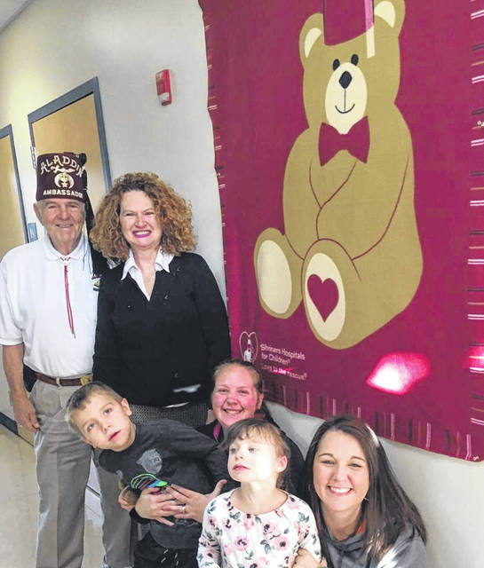 The Gallipolis Shriners provide rides to medical appointments free of charge for children and families who qualify. Information is available at the Bossard Memorial Library or the Guiding Hand School. Pictured are Guy Guinther of the Shriners, Gallia Board of DD Superintendent Pamela Combs, Benjamin Ingles, Heather Dennie, Allie Newell and Kayla Ingles. Shriners donated a bear blanket to the school.