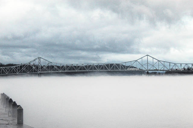 Fog settles in on Wednesday evening, obscuring the Ohio River from view. Pictured is the Silver Memorial Bridge as seen from Riverfront Park in Point Pleasant, W.Va.