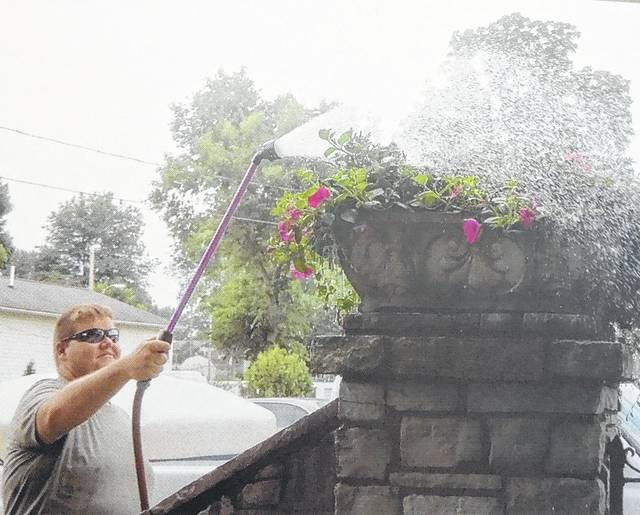 Gallipolis in Bloom started its community beautifying mission in the early 2000s. Pictured are some of the organizations flowers being watered.