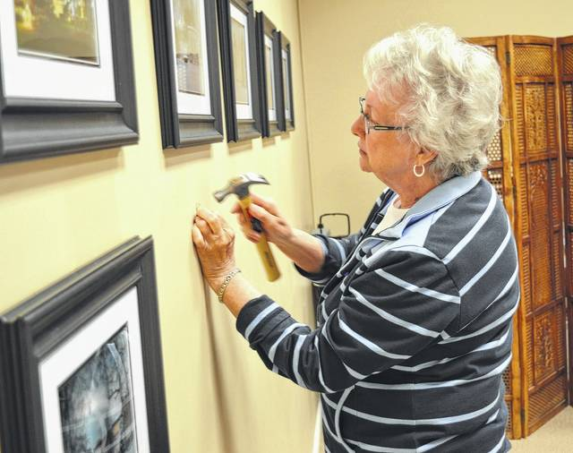Mary Lee Marchi tacks up some of her work at a previous art show.