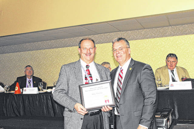 Mike McCalla, former director to the Gallia County Agricultural Society was recently recognized as the Outstanding Fair Supporter to the Gallia County Junior Fair. In addition, Mike was selected as one of the Ohio Department of Agriculture Director's Award for Innovation and Excellence Award winners at the annual Ohio Fair Manager's Association Convention. The Director's Award was given to select individuals who demonstrated forward-thinking achievements at fairs across Ohio. McCalla served as a director to the Gallia County Agricultural Society for 24 years including two years as President and treasurer for 18 years. Pictured above is Tim Massie, left, Secretary of the Gallia County Agricultural Society, accepting the award, on behalf of McCalla who could not attend, from Ohio Department of Agriculture Interim Director Tim Derickson, right.