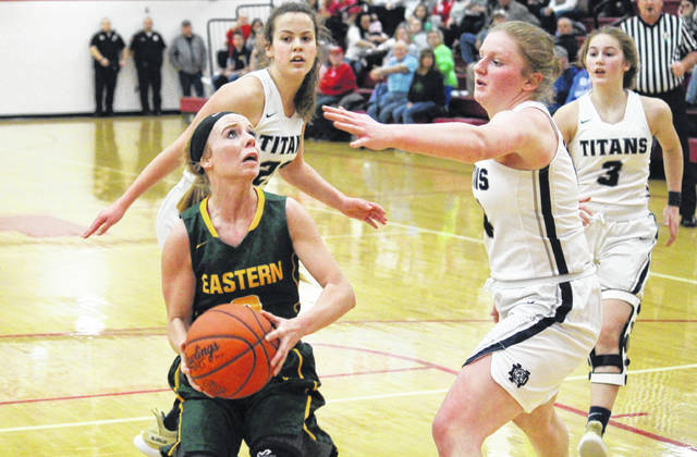 Eastern senior Jess Parker (left) goes in for a layup in front of a trio of Lady Titans, during the D-4 district final on Feb. 28 in Jackson, Ohio.