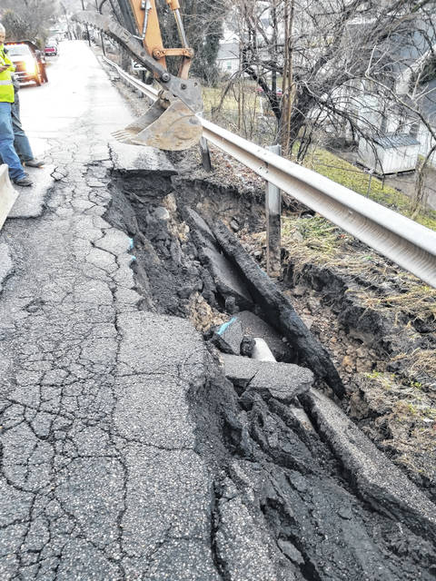 Slippage and damage to Mill Street can be seen. The damage resulted in the closure of the roadway to all traffic.