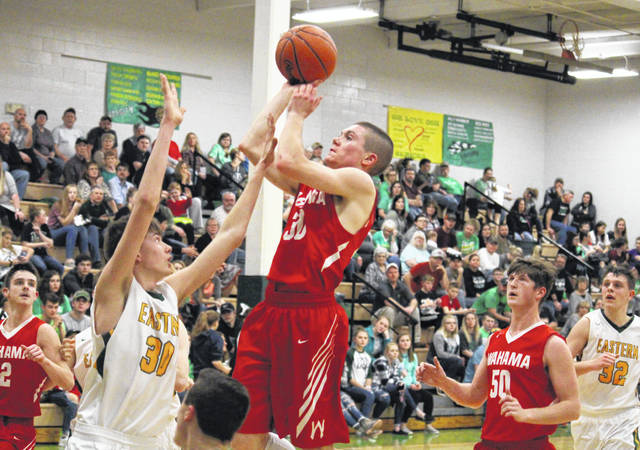 Wahama's Jacob Lloyd (center) shoots a two-pointer over Eastern's Garrett Barringer, during the Eagles' 37-36 victory on Feb. 5 in Tuppers Plains, Ohio.