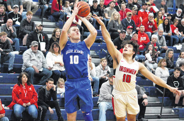 Gallia Academy senior Justin McClelland (left) attempts a two-pointer over Jackson senior Nevan Yates (right), during the D-2 sectional final on Feb. 23 in Londonderry, Ohio.