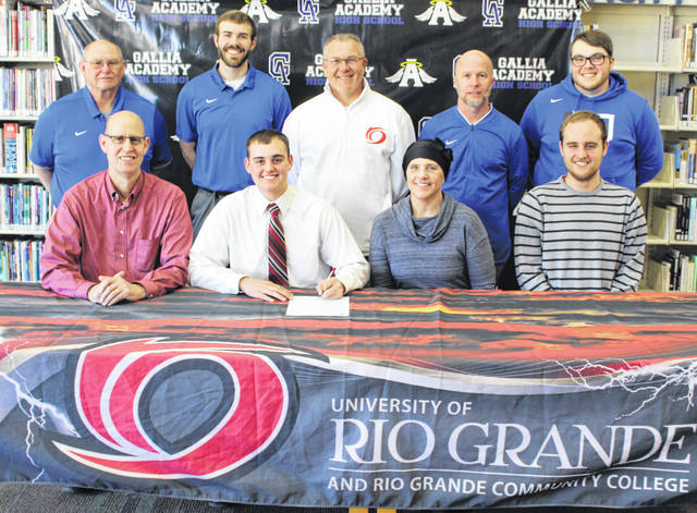 Gallia Academy senior Josh Faro, seated second from left, will be continuing his baseball career after signing with the University of Rio Grande on Monday, March 18, 2019, at the GAHS library. Josh is joined in front by his parents, Dave and Bev Faro, and brother Jake Faro, right. Standing in back are GAHS assistant Jack James, GAHS baseball coach Justin Bailey, Rio Grande baseball coach Brad Warnimont, former GAHS coach Rich Corvin and GAHS assistant Jeremy Brumfield.