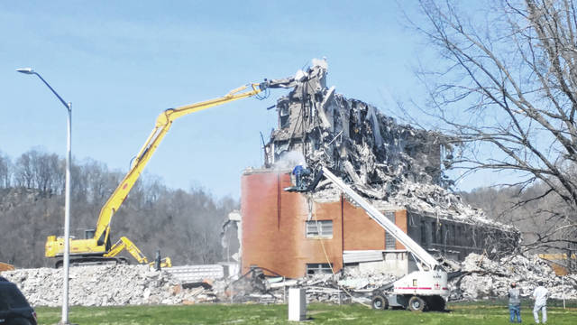 Crews work to tear down the old medical and surgical building on the Gallipolis Developmental Center property, Thursday.