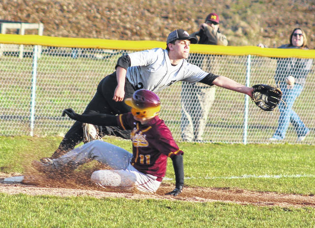 Meigs junior Cory Cox (11) slides safely into third base as an errant throw gets past River Valley sophomore Joel Horner during the ninth inning of Monday night's TVC Ohio baseball contest in Bidwell, Ohio.