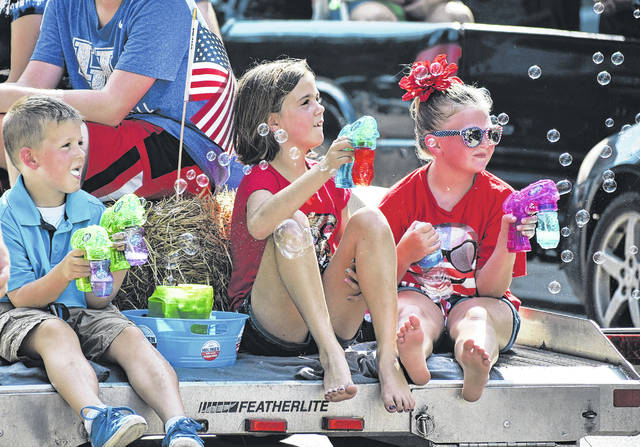 A trio of children blow bubbles from a float during the parade at last year's River Rec Festival.