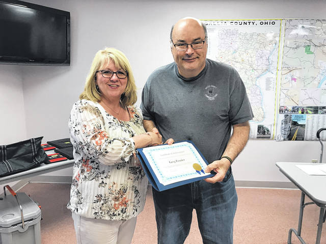 Greg Frazier was named the 2019 Gallia Dispatcher of the Year. At left is Sherry Daines, Gallia 911 Communications Director. Frazier also served as a Gallipolis police officer and is a former EMT.