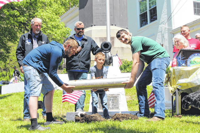 Zach Davis, left, and Nathan Cook, right, with the assistance of Porter Webb, recreate the photo of the burying of the 175th anniversary.