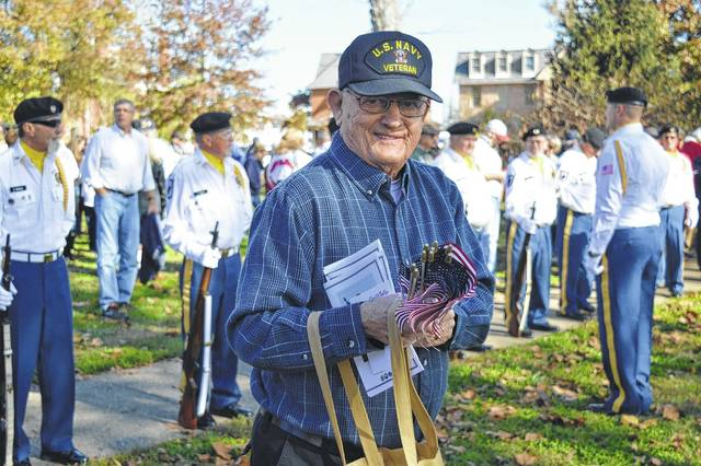 Marvin Vanderberg passes out American flags at Veterans Day 2016 in Gallipolis City Park.
