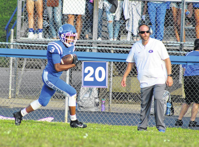 Gallia Academy sophomore James Armstrong (3) returns a kickoff in front of head coach Alex Penrod, right, during the first half of a 2018 Week 2 football contest against River Valley at Memorial Field in Gallipolis, Ohio.