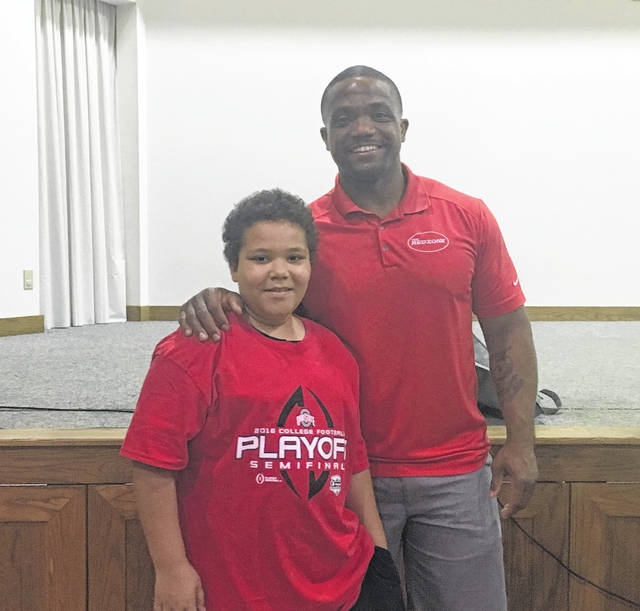 Former OSU and NFL football player Maurice Clarett took time to pose for photos at the event on Thursday evening at the Middleport Church of Christ. Here, Clarett is pictured with Xavier Armstrong.