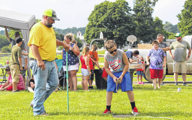 Hunter Jarrell prepares to jump his frog during the Frog Jump Contest on July 4th at Racine's Star Mill Park. Jarrell took first place in his age group with a jump of 11 feet, 1 1/2 inches.
