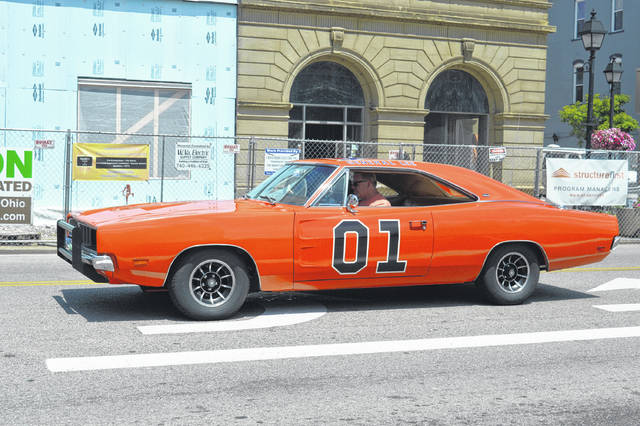 A Charger painted after the iconic Dukes of Hazzard's General Lee rolls by on Second Avenue