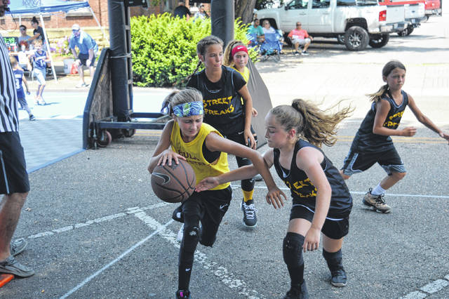 One player defends the ball as she attempts to juke an opponent.