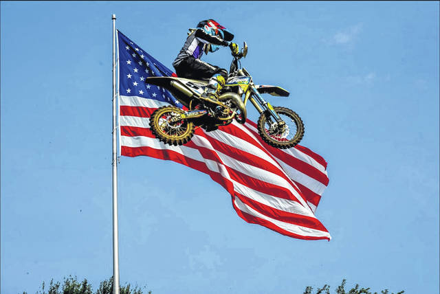 Gage Spaun leaps past an American flag.
