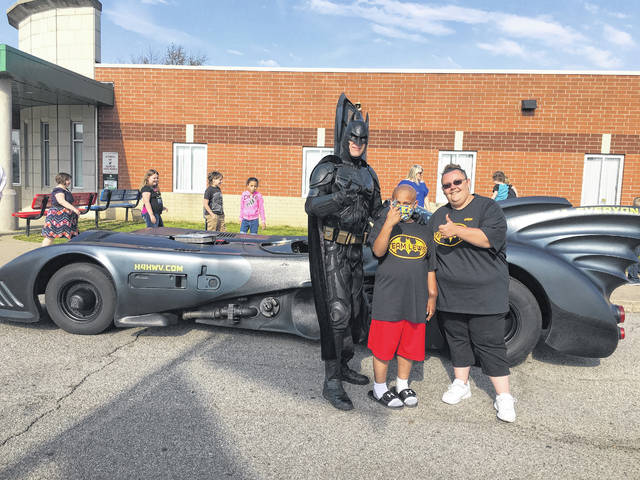 Lewis Bryant is pictured here in front of the Batmobile with his mother Tabitha Halley and Heroes-4-Higher West Virginia Batman John Buckland.