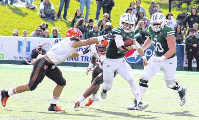 Ohio quarterback Nathan Rourke breaks away from two Falcon defenders, in front of teammate Austen Pleasants (60), during the Bobcats' 49-14 victory on Oct. 20, 2018, in Athens, Ohio.