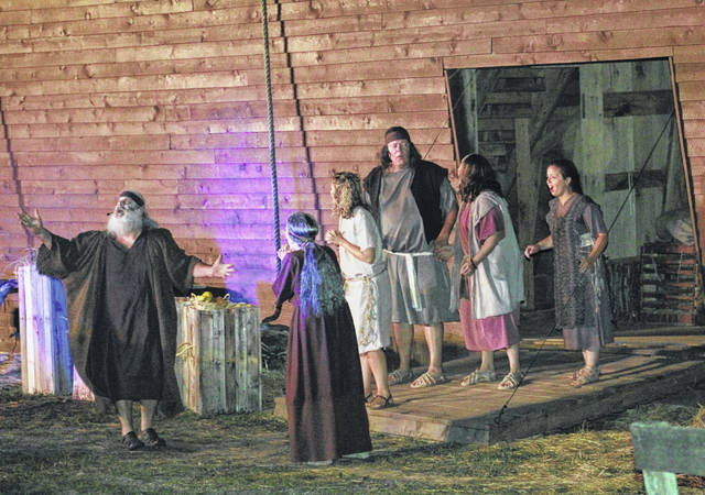 Noah, far left, speaks with his family members as they prepare to enter the ark.